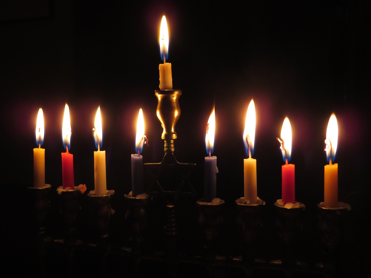 A menorah with all eight candles and the leading candle (shamash) lit in a dark room