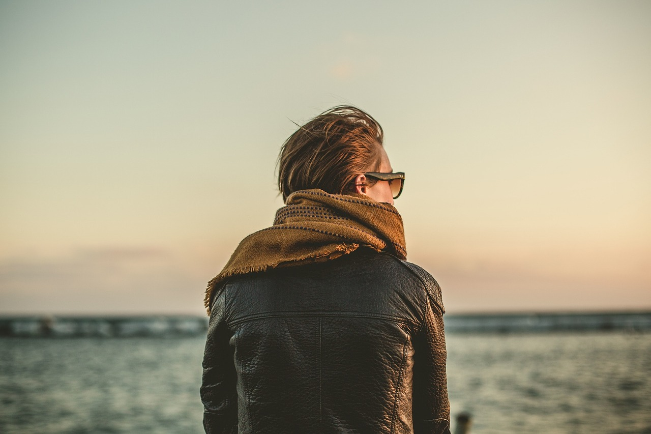 A woman with short brown hair stands facing the ocean with her back to the camera, wearing sunglasses, a brown scarf and a leather jacket