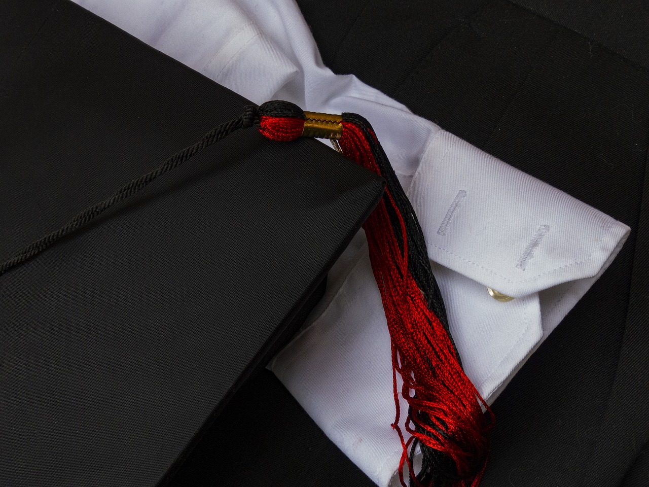 A close-up shot of a graduation cap with a red-and-black tassel on top of a black graduation robe and the sleeve of a white button-down