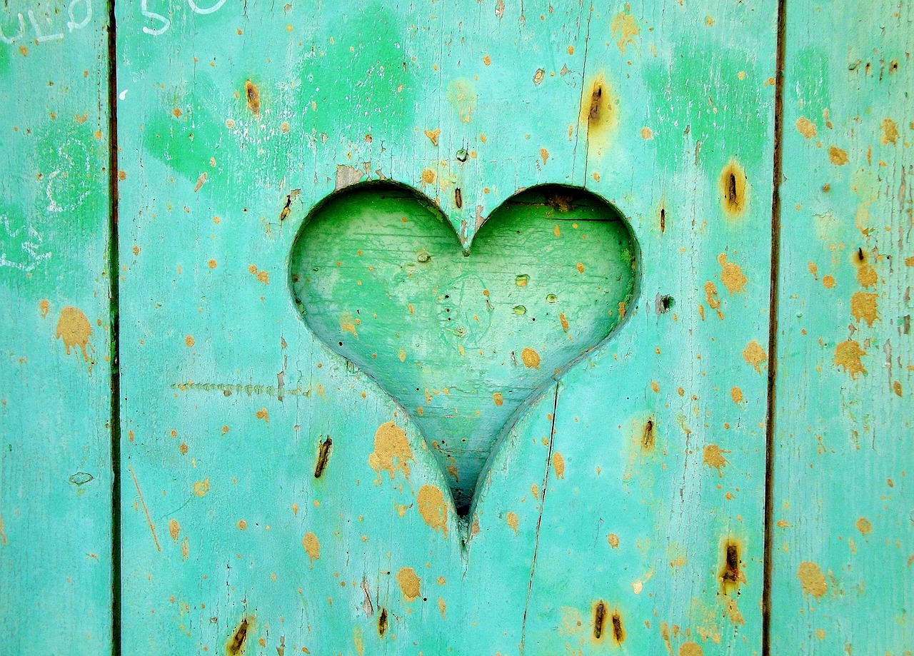 A heart carved into worn blue-painted wood