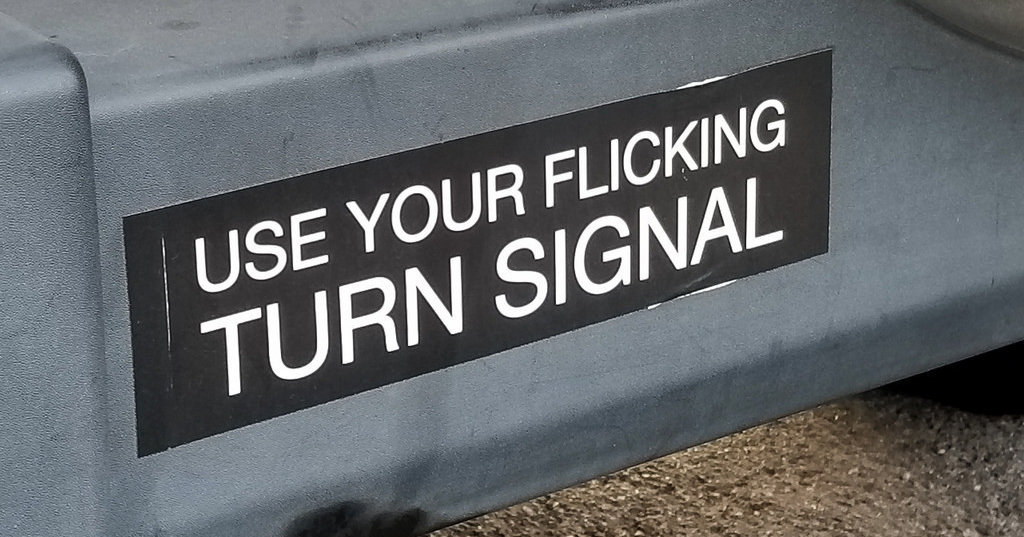"Black bumper sticker with white text reading ""Use your flicking turn signal"""