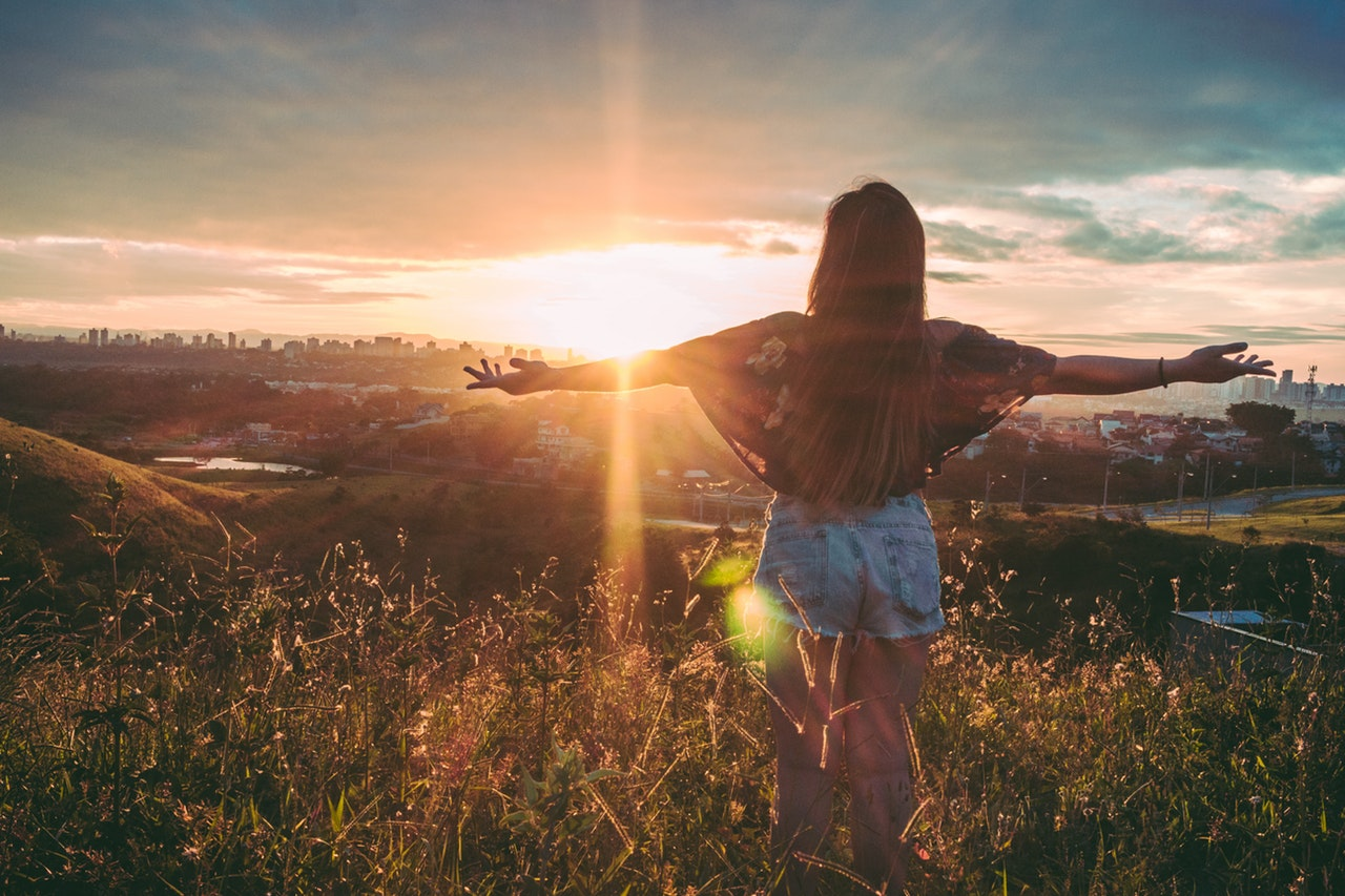 A girl with long hair standing in a field with her back to the camera, arms out wide on both sides, facing the sunset
