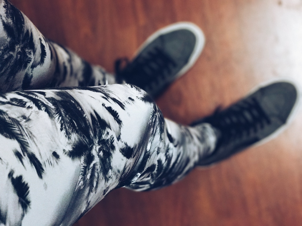 A girl's legs in black-and-white palm tree-patterned leggings and charcoal grey sneakers.