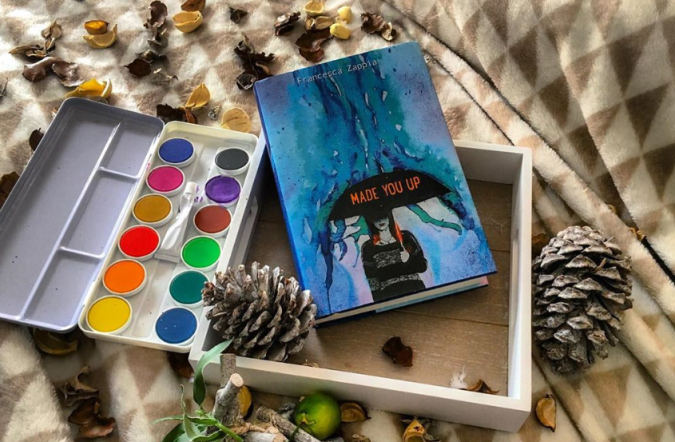 Made You Up by Francesca Zappia book in a shallow white wooden box atop a brown-and-white fuzzy blanket, surrounded by pinecones, a lime, flower petals, and a paint set.