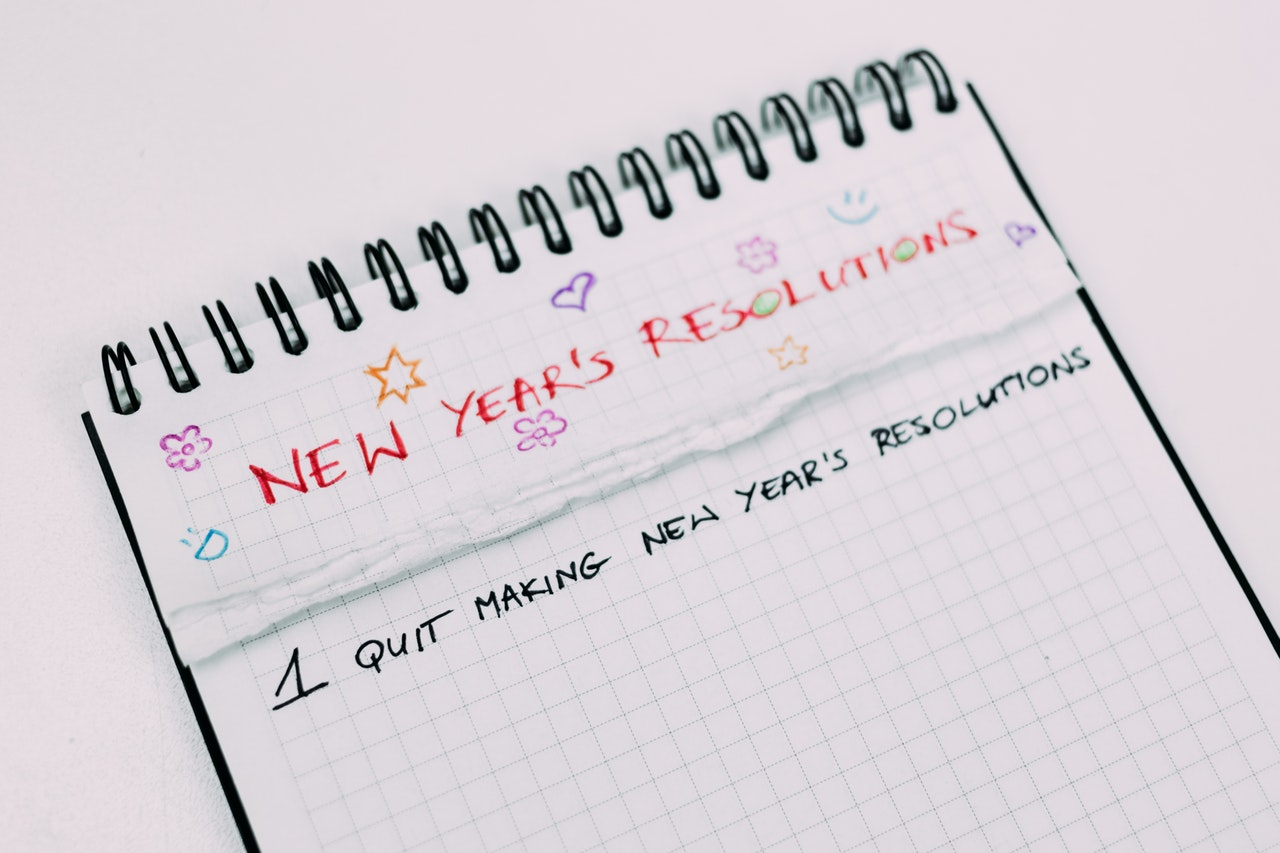 "A white grid notepad with colorful small doodles and ""NEW YEAR'S RESOLUTIONS"" written atop it, with several pages ripped out beneath the title page to reveal a page reading ""1: Quit making New Year's resolutions"""