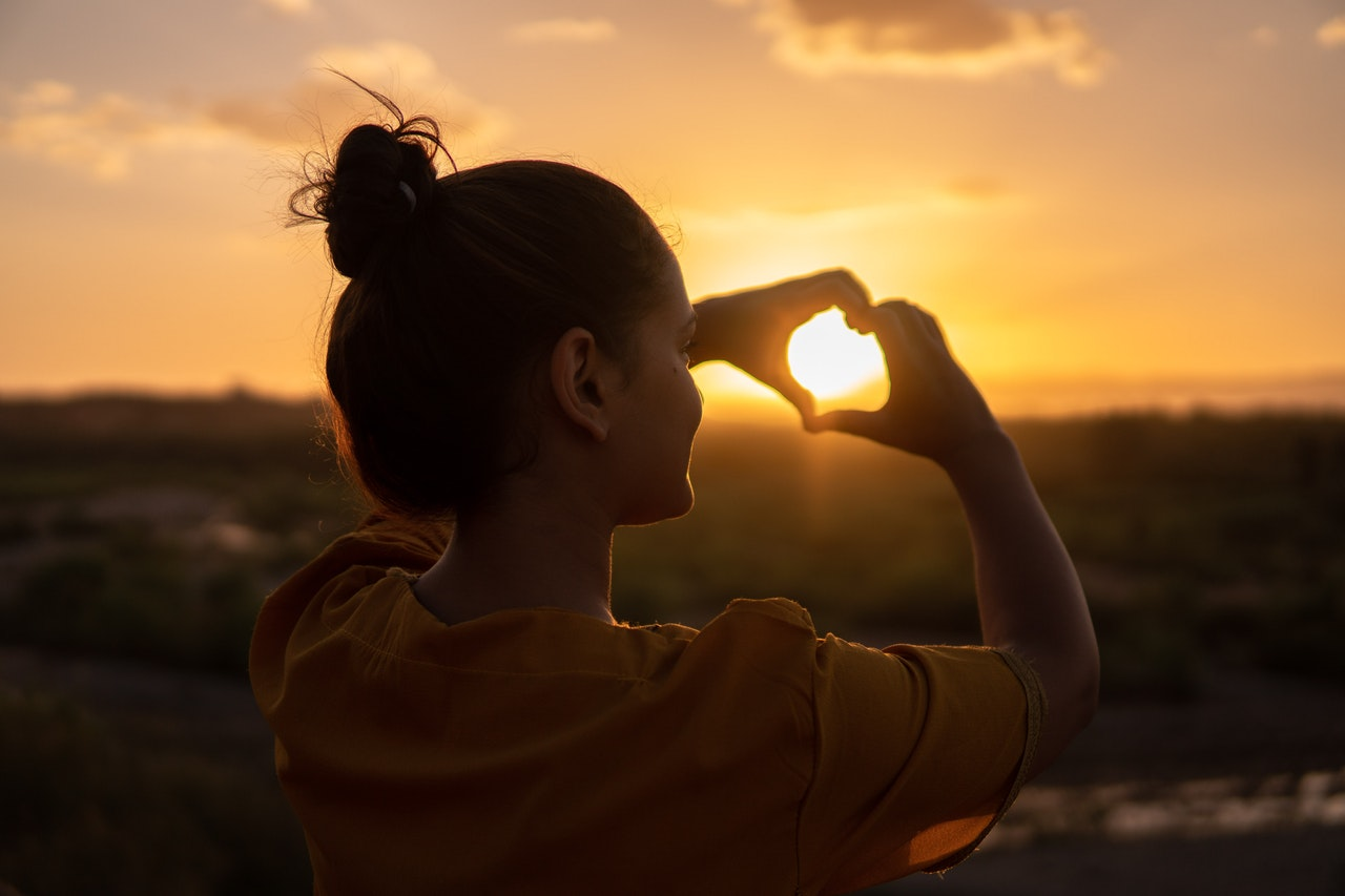 A woman with her back to the camera holds her hands up to outline the sunset in the shape of a heart