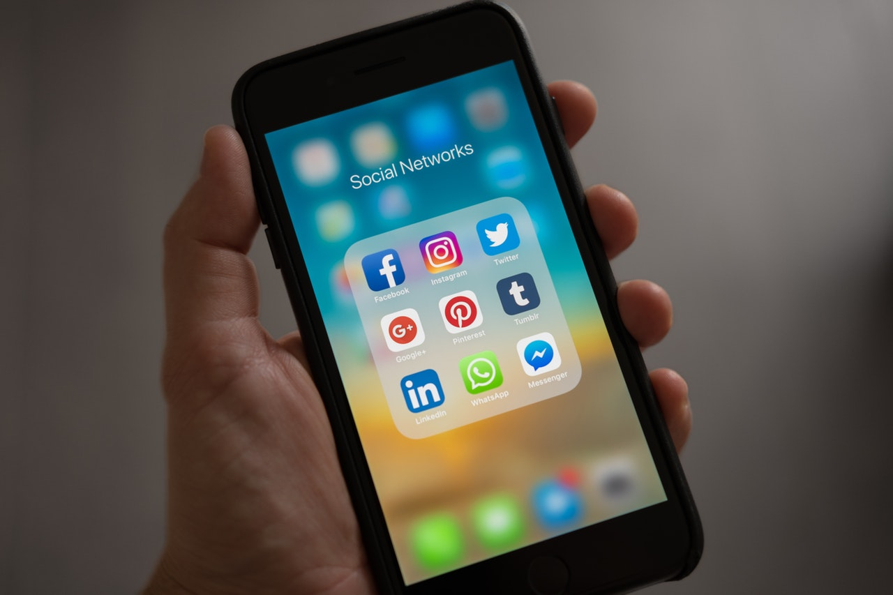 "Hand holding iPhone screen up to the camera to show a folder titled ""Social Networks,"" filled with social media icons (Facebook, Instagram, Twitter, Google+, Pinterest, Tumblr, LinkedIn, WhatsApp, and Facebook Messenger)"