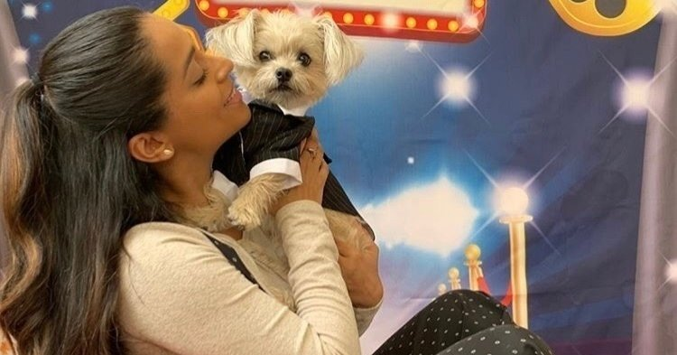 YouTuber Lilly Singh holds up her dog Scarbro and looks at him lovingly while seated in front of a red carpet backdrop