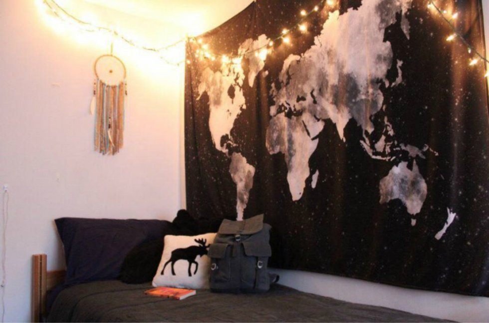 A white-walled college dorm room featuring a string of twinkly lights and a dreamcatcher hanging near the head of the bed, a tapestry with a black-and-white map of the world, and a dorm bed with black sheets and a backpack on it.