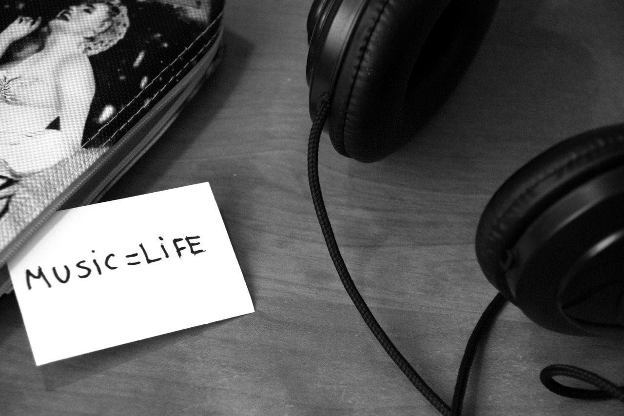 "Black and white picture of headphones, a pen case and a small piece of paper with ""Music=Life"" written on it"