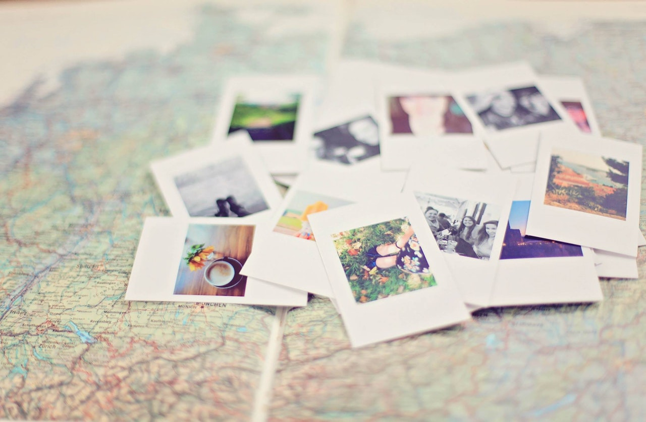 A pile of Polaroid shots on top of a map, the edges of the photo blurred