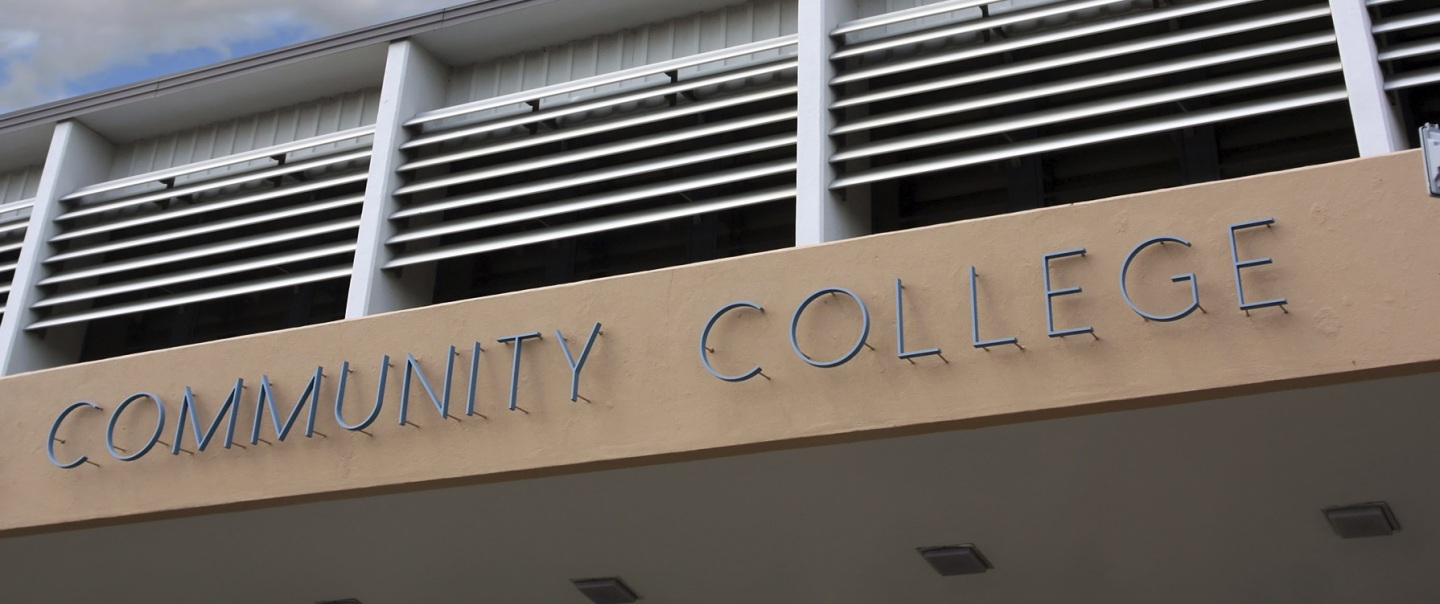 "The front of a community college building with the words ""Community College"" lettered on the wall"