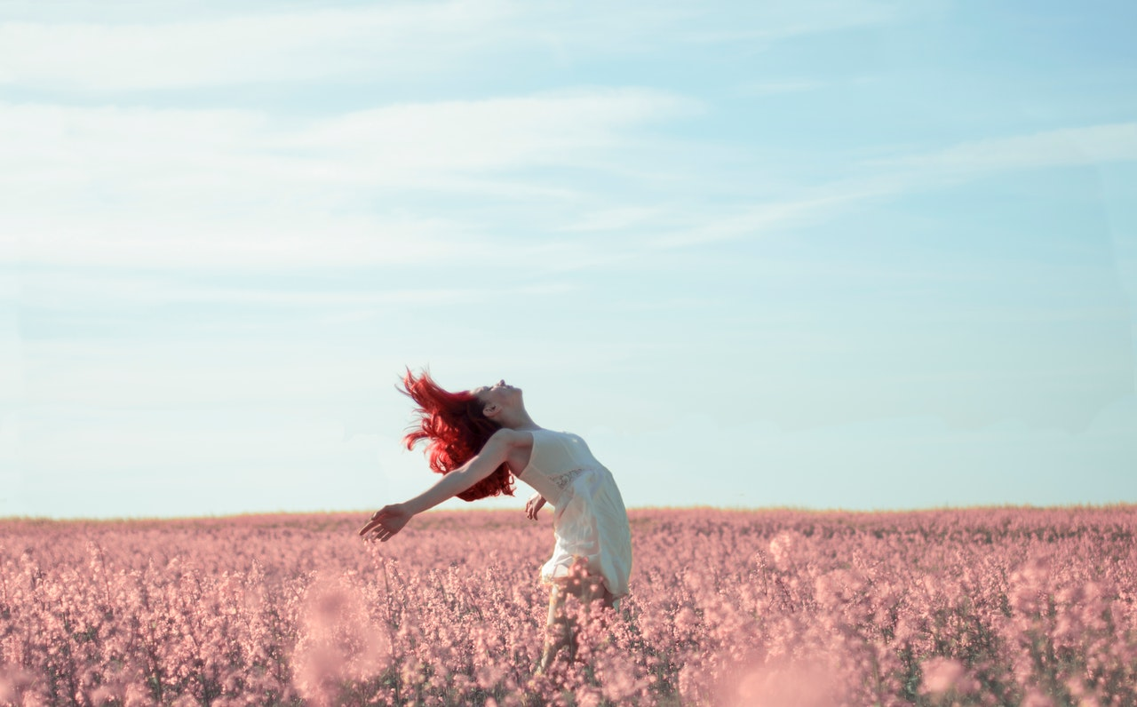 A woman with bright red hair and a white dress jumps up with her head tilted back to the clear blue sky in a field of pink flowers