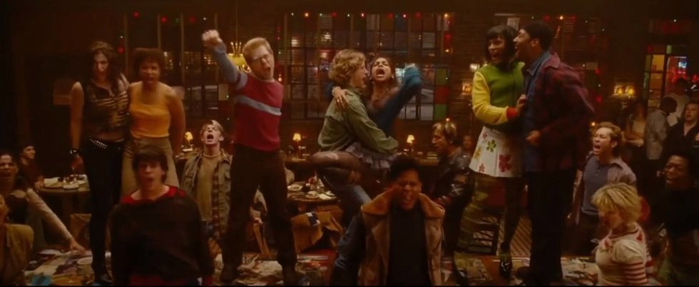 "Screenshot from the ""La Vie Boheme"" song/scene in the movie musical ""Rent,"" with the main cast standing on a long table (Idina Menzel as Maureen, Tracie Thoms as Joanne, Anthony Rapp as Mark, Adam Pascal as Roger, Rosario Dawson as Mimi, Wilson Jermaine Heredia as Angel, Jesse L. Martin as Collins)"