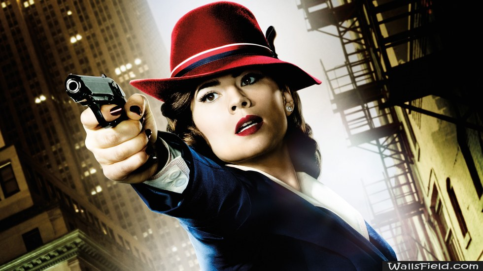 Peggy Carter, played by Hayley Atwell, in her signature red hat, blue coat and red lipstick pointing a gun just left of the camera