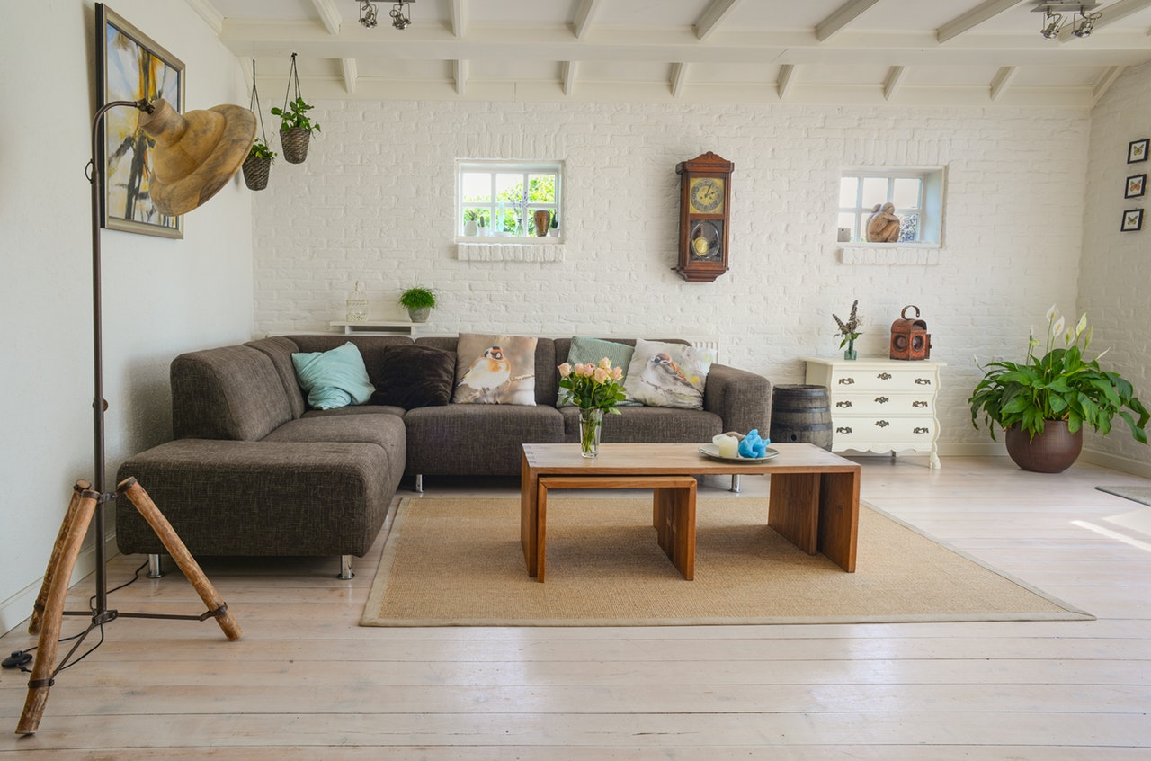 An apartment living room with white brick walls, a brown L couch, a wooden coffee table, and assorted other living room furniture