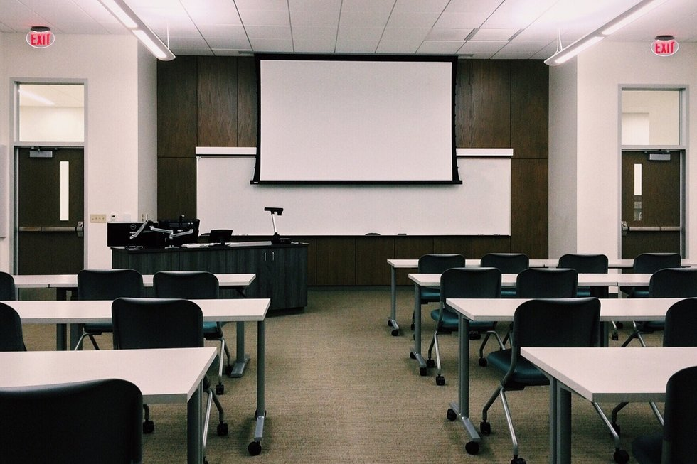Stark college classroom with white tables, black chairs, a projector screen pulled down over the whiteboard, two doorways with dark wood paneling in between