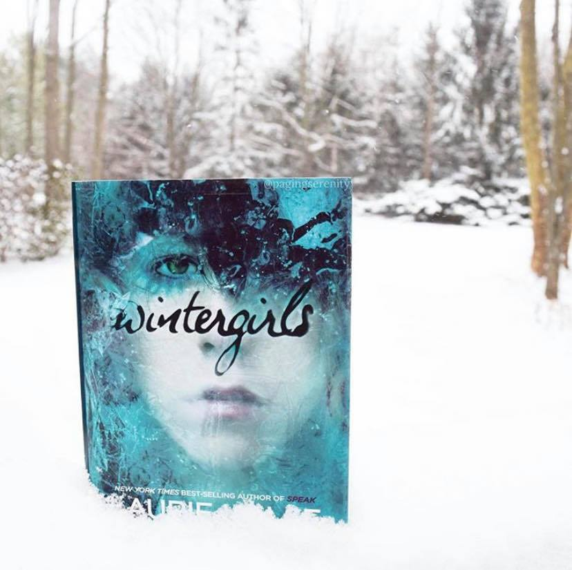 "Copy of ""Wintergirls"" by Laurie Halse Anderson standing in a snowy field with snow-covered trees behind it"