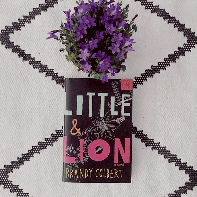 """Overhead shot of """"Little & Lion"""" by Brandy Colbert book resting on a black-and-white large diamond patterned tablecloth with a pot of purple flowers in the top diamond and the book in the bottom diamond"""