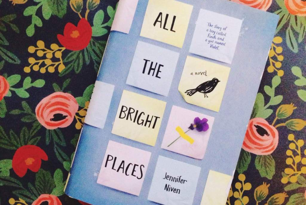 "Hardcover copy of ""All the Bright Places"" by Jennifer Niven against a black and floral background"