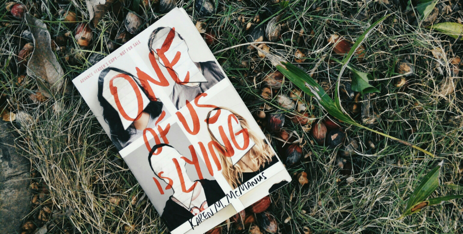 "Paperback of Karen McManus's murder mystery book ""One of Us is Lying"" resting atop in dead grass and fallen, overripe fruit"