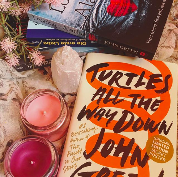 "Hardcover copy of ""Turtles All the Way Down"" by John Green nestled next to 2 pink candles, a pink rock, and a stack of other books"